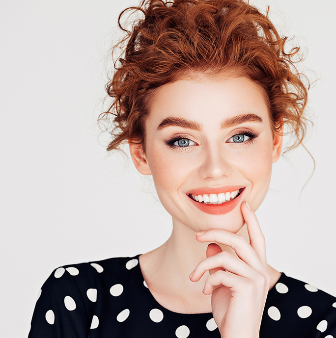 Redhead woman smiling with white teeth