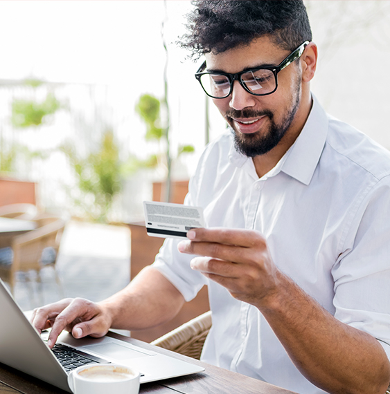 Man with glasses online shopping with his credit card