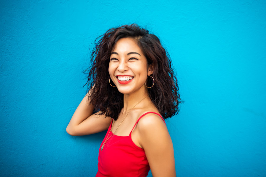 Brunette woman in a red tanktop smiles against a blue wall with dental implants in Hickory Hills, IL